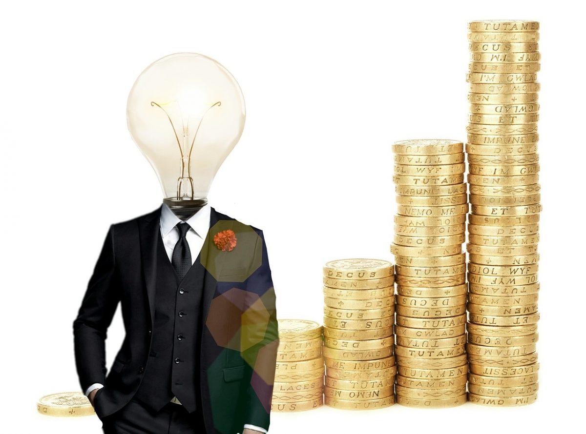 Geld sparen mit Wechselpilot.de ein Erfahrungsbericht. Abgebildet ein schlaues Kerlchen mit Glühbirnenkopf und aufgestapelte Münzen.